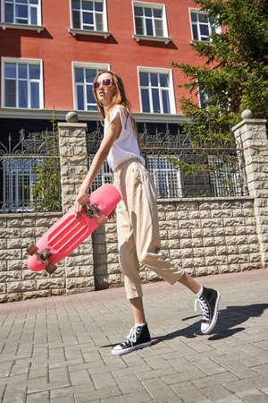 Girl with skateboard. Town landscape. Black sneakers. New normal travel. Eco trip. Local city traveller. Staycation lifestyle. Extreme skate riding. Road to school