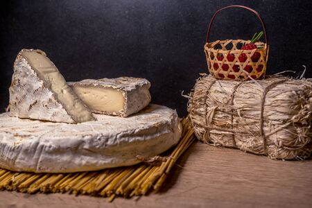 Cheese Camambert with raspberry basket. Rustic set on black backdrop. Healthy fresh nutrition. Healthy food background.
