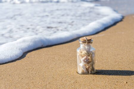 bottle with shells on the beach in the waves