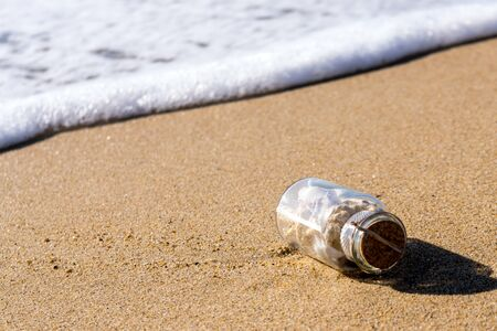 glass bottle with see shells washed ashore