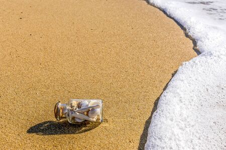 glass bottle with shells on the seashore in the waves