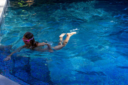 Little girl swims in the blue swimming pool. Hight quality photo