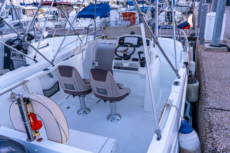 Hight-speed motor boat on the pier in the port, view of the steering cabin, two seats and a steering. Mediterranean coast