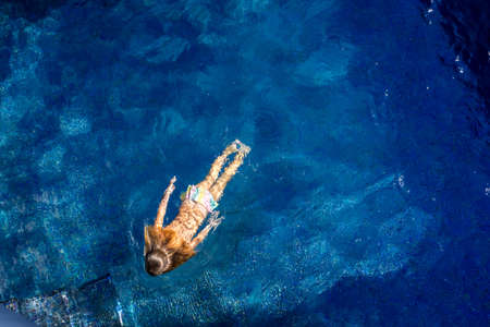 Soft focus background. Little girl swims in the blue swimming pool. Hight quality photo