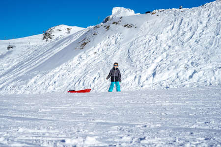 Boy with red sled in snow. Snow mountain background. Winter holidays Reklamní fotografie