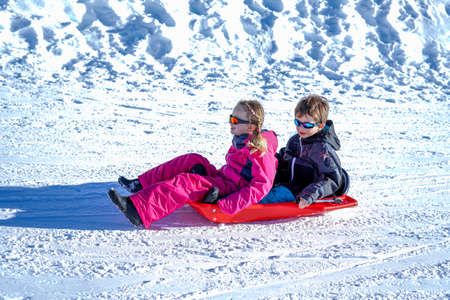 Two joyful kids sledding down the hills on a winter day. Brother and sister Reklamní fotografie