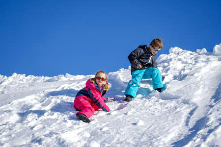 Two joyful kids playing on the snowing mountain on a winter day. Brother and sister Reklamní fotografie