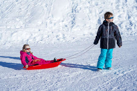 Brother pulling his sister kids toboggan sled snow. Little girl and boy enjoying sleigh ride. Child sledding. Children play outdoors in snow. Kids sled.