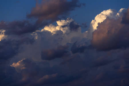 Blue sky with white and dark clouds. Heavenly dreamy fluffy colorful fantasy clouds.