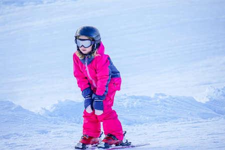 Little girl is learning to ski in ski resort. Winter season. Stockfoto