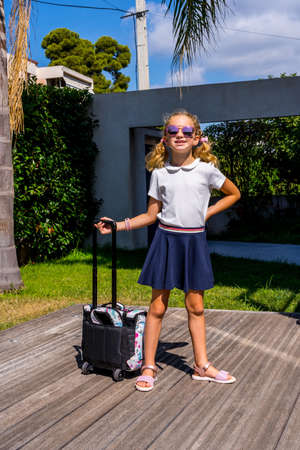 Portrait of happy caucasian young girl going to school. Closeup face of smiling schoolgirl with sunglasses looking at camera. Back to school Standard-Bild