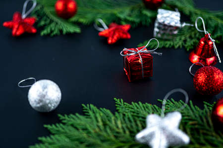 Christmas composition with red gift. Fir tree, gift and toys. Winter holiday theme. Space for text. Blurred focus background. Imagens