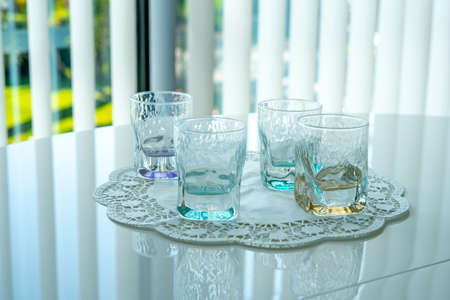 Top view of crystal glasses on a white lace napkin. White table background. High quality photo