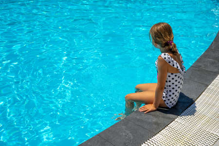 Happy little girl near the swimming pool. Summer vacation. Travel. High quality photo