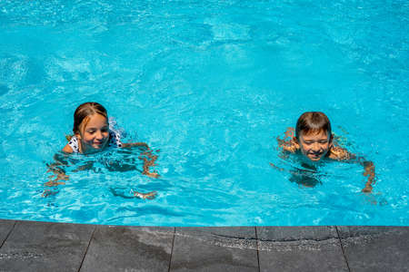 Children swim in the swimming pool. Brother and sister spend time together. Hight quality photo