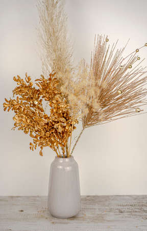 Composition of pampas grass with New year golden branch decoration in a vase on a white wall and wooden table background. Holidays decor concept. High quality photo