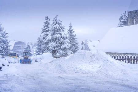 Auron, France 01.01.2021 A harvesting tractor cleans snow in a ski resort on the road in a heavy snowfall. Mountain village. High quality photo Reklamní fotografie