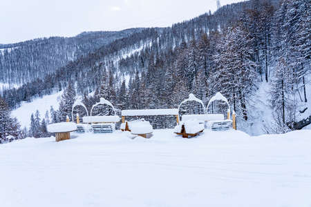 Outdoor picnic table and chairs covered in a thick layer of untouched deep snow. Snow-covered park on the mountains. High quality photo.