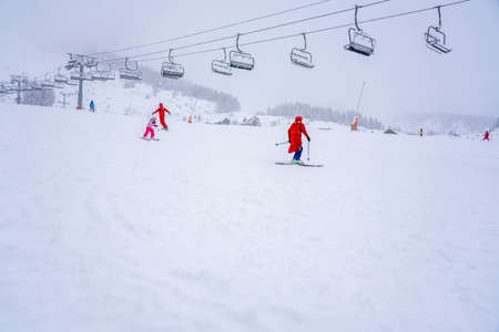 Downhill skiing during a heavy snowfall. Professional ski instructors and children on a resort slope in mountains. Ski race for young children. Blurred focus background. High quality photo