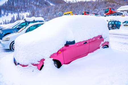 Auron, France, - 02.01.2021: After heavy snowfall car covered with snow standing at city parking. High quality photo