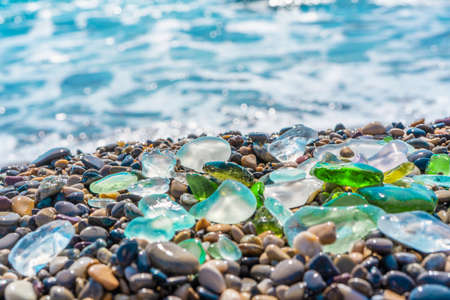 Natural polish textured sea glass and stones on the seashore. Azure clear sea water with waves. Green, blue shiny glass with multi-colored sea pebbles close-up. Beach summer background.