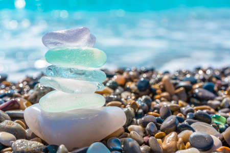 Sea glass stones arranged in a balance pyramid on the beach. Beautiful azure color sea with blurred seascape background. Meditation and Harmony concept