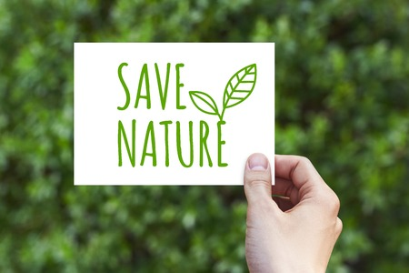Hand holds a paper card with Save Nature on abstract nature blur background. It can be used as a mockup.