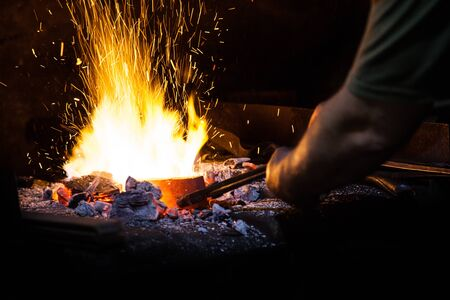 Unrecognizable Hands of Smith Preparing Metal on Anvil for Forging with spark fireworks