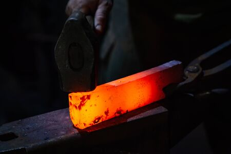 The blacksmith manually forging the red-hot metal on the anvil in smithy Stock fotó