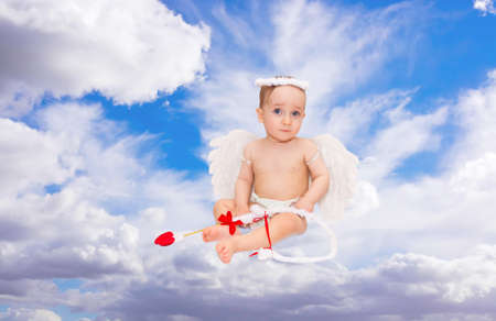 Cute little boy dressed as Cupid on blue sky  photo