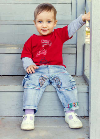 Beautiful child sitting on the wooden stairs photo