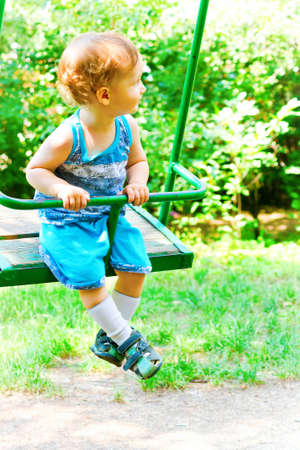 Beautiful child swinging on a swing in the Park photo