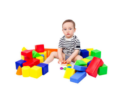 Little boy puts colored cubes and pyramid isolated on white background photo