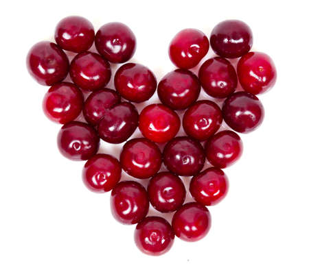 A lot of ripe cherries heart shaped isolated on white background photo