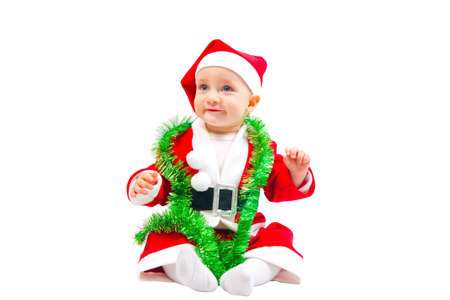 Adorable baby in the costume of Santa Claus is sitting on the floor isolated on white background photo