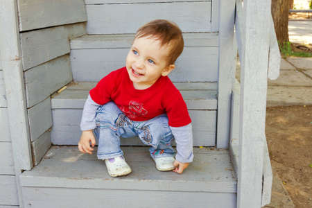 Adorable little boy sitting on the wooden stairs photo