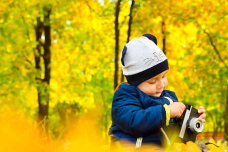 Adorable baby with a film camera in his hands in the Park. Autumn season photo