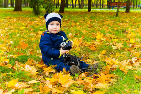 Cute boy with a film camera sits on fallen leaves in the Park. Autumn season photo