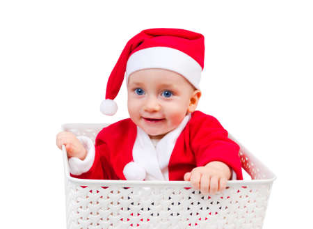 Funny child in Santa Clause cap sitting in a box isolated on white background photo