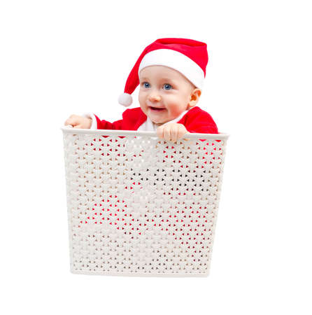 Photo of surprised boy in Santa Clause suit hiding in a box isolated on white background photo