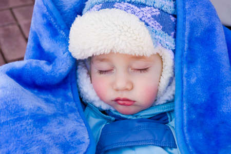 Baby sleeps in a stroller on a walk in the fresh air photo