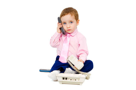 Beautiful child in a business suit answers on a few phone calls simultaneously isolated on white background photo