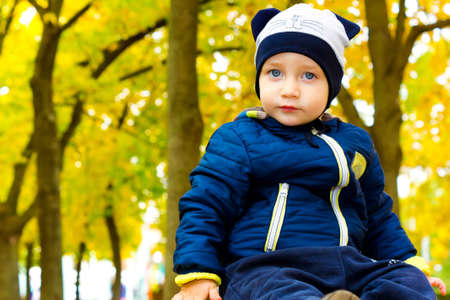Beautiful child in a funny hat in autumn Park photo