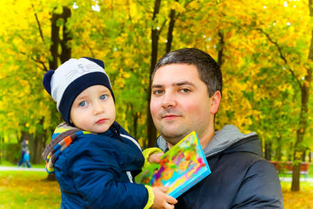 Caring father holds his child with a book photo
