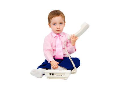 Charming boy talking on the phone in a business suit isolated on white background