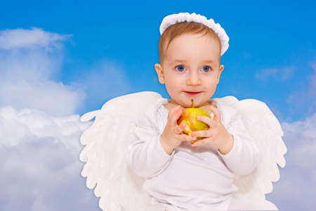 Cute baby cupid with angel wings in the clouds photo
