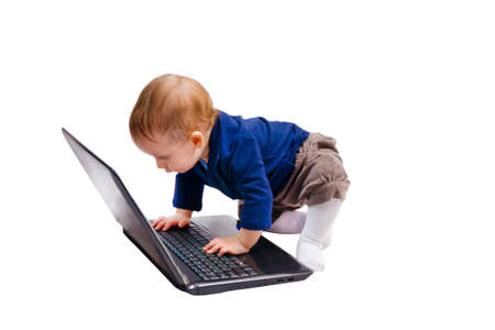 Cute baby playing with a laptop isolated over white background photo