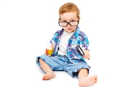 Cute child in glasses with a magnifying glass is experimenting with apple isolated on white background photo