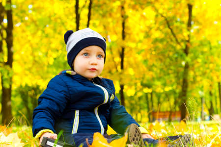 Cute child sitting in the autumn Park photo