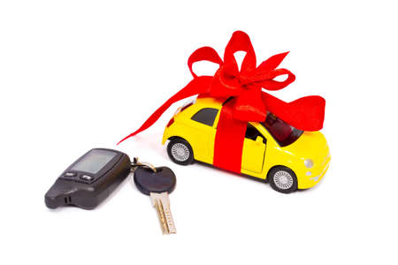 A gift. A modern car with a red bow and keys isolated on white background photo